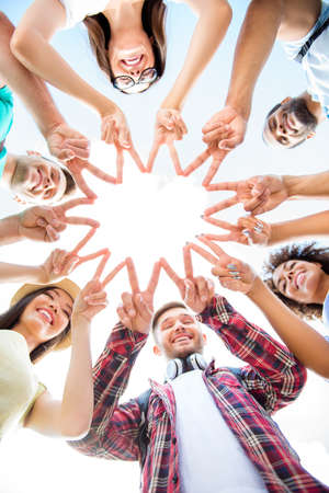 Unity and connection of people. Topview of multi ethnic students friends, putting their fingers together, wearing casual clothes, otdoors on a sunny day. Conception of successful teambuilding Stock fotó