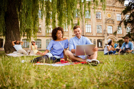 Couples of international students are studying after lectures, sitting in the park, chatting, smile, enjoying, helping each other with studies. All dressed in comfortsble casual wear, sunny spring day