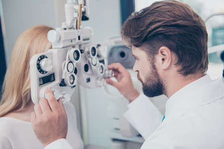 Close-up of brunet bearded doc optometrist adjusting phoropter for young blond female patient. Eye sight and healthcare