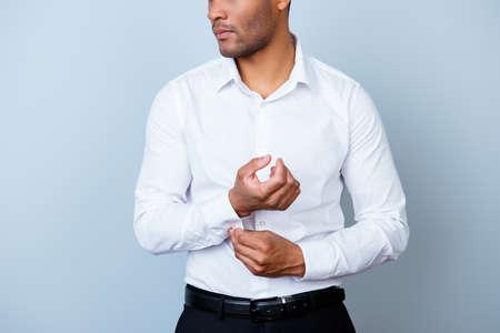 彼の cuffl のインク、純粋な光を背景に彼のスタンドを固定、スーツの若いハンサムなアフリカの実業家弁護士のトリミング、写真を閉じます。だか 写真素材