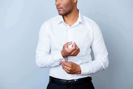 Sluit omhoog bebouwde foto van jonge knappe Afrikaanse zakenmanadvocaat in een kostuum, bevestigend zijn cuffl inkt, bevindt hij zich op zuivere lichte achtergrond. Zo volwassen en viriel, warm en zelfverzekerd