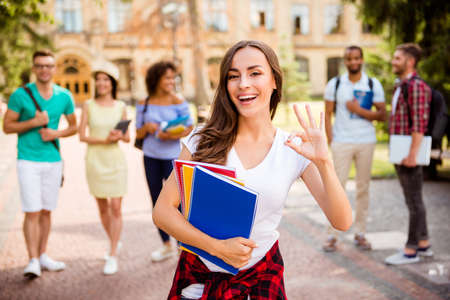 Happy cute brunette caucasian girl is smiling and gesturing ok sign, standing near university building, her friends are behind, they passed exams, so cheerful and carefree!
