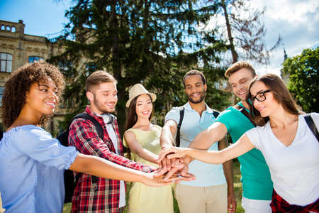 We will do it together! Six happy international students putting their hands on top of each other, wearing casual outfits, walking after studies outside in a sunny spring day. Conception of successful teambuilding