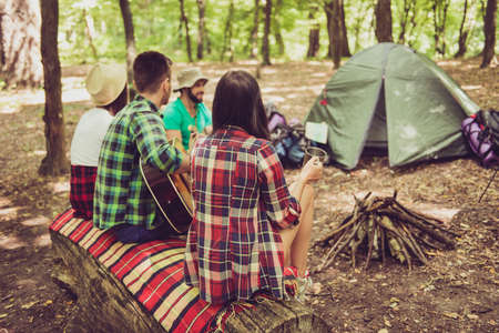 Rear view shot of two couples hiking together, sitting near the fire place in a camp with a guitar, tent, blanket, backpacks
