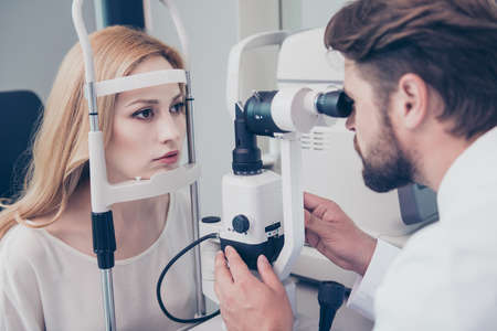 Concentrated brunet bearded optician with non contact tonometer is checking blond`s lady patient intraocular pressure at eye clinic. Health care, medicine, eye sight and technology concept