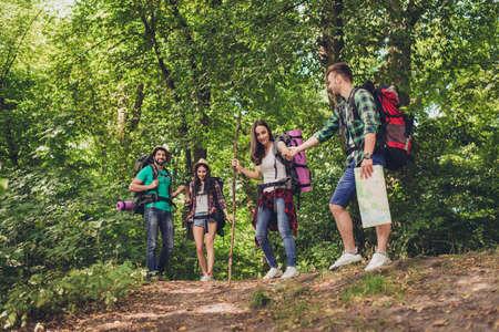 Confianza, amor, apoyo, ayuda, concepto de amistad. Cuatro amigos están caminando en el bosque de la primavera, el tipo está sosteniendo la mano de la dama, todos están emocionados y ansiosos Foto de archivo - 86215217
