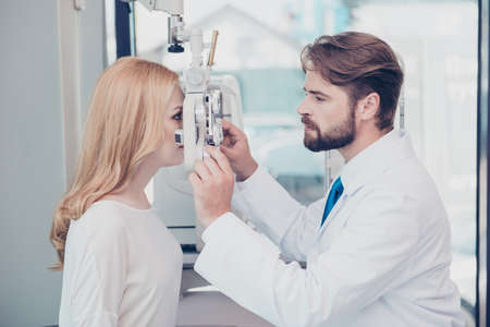 Health care, medicine, eye sight and technology concept. Side profile photo of brunet bearded optician checking blond`s lady patient intraocular pressure at eye clinic Stock Photo