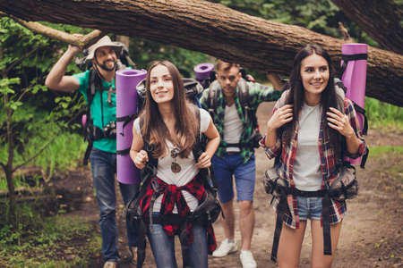 Close up photo of four friends enjoying the beauty of nature, hiking in wild forest, looking for a nice place for camp, smiling, exploring jungle trail