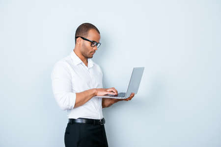 Confident pensive young mulatto americano market broker is looking at his laptop, standing on the pure background, being pensive and severe