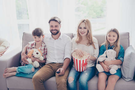 Young beautiful couple of blondie and brunette guy are watching family movie with kids, eating popcorn at light cozy home, smiling, enjoying Stock Photo