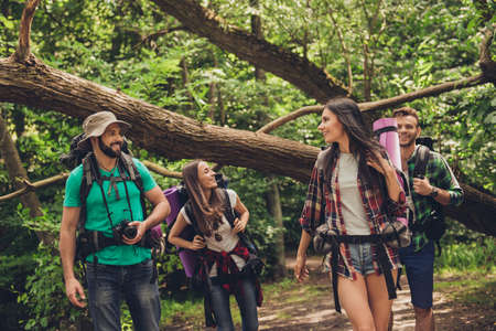 Low angle close up photo of four friends enjoying the beauty of nature, hiking in wild forest, looking for a nice place for camp, smiling, exploring, jungle trail Stock Photo