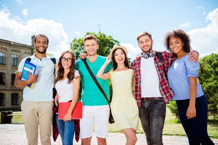 Compañero de clase, amistad internacional, verano, comunicación, educación y concepto adolescente. Grupo de adolescentes estudiantes alegres en trajes casuales con cuadernos están de pie fuera del campus Foto de archivo - 86215254