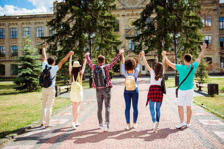 Successful future for smart youth! Six attractive young bachelors are near university, standing near the building, with raised arms, celebrating, wearing casual smart Stok Fotoğraf