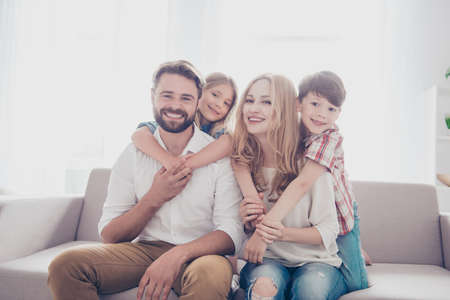 Family portrait of four. Happy parents are piggy backing  thier cheerful kids -  blond small girl, brunet boy, sitting at the sofa at home, all smiling Stock Photo