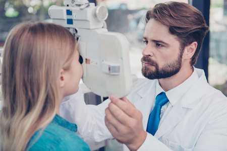 Close up of brunet bearded doc optometrist adjusting phoropter for small blond girl patient. Eye sight and healthcare concept