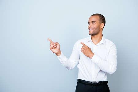 순수 밝은 파란색 배경에 젊은 쾌활한 성공적인 아프리카 사업가 웃고, 공식적인 마모를 입고 copyspace 그의 손가락으로 가리키는