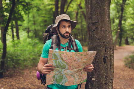 Male brunet bearded confused tourist got lost in the forest, holding map, looking far, trying to find the way. He has a backpack, all needed for overnight stay. Search the trail way Stok Fotoğraf