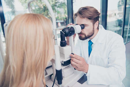 Healthcare, medicine,  eyesight and technology concept. Eye doctor is checking the vision of blond female patient with ophthalmologic device in the cabinet Stock Photo