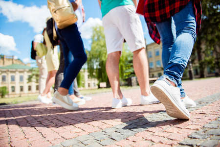 Cropped close up low angle photo shot of six student`s legs, walking on the cobbles. Sunny spring day, students are going to campus together Stock Photo