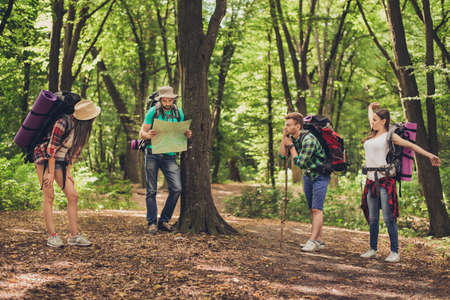 Four tourists stopped for rest in the forest, holding map, trying to find the way, disscus it, all having backpacks, mates, relaxing after tiring walk Stock fotó