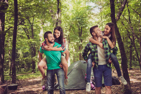 Two lovely couples, nice forest view. Guys are piggybacking their girlfriends, so happy, smiling