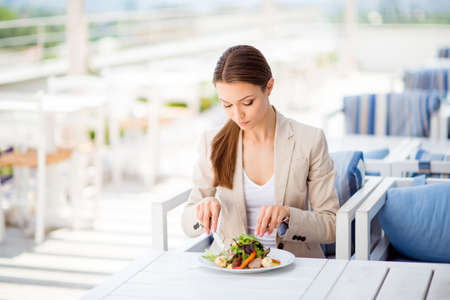 pedant: Serious business lady is having lunch on an open air light terrace outdoors. She is in a formal wear, eating salad Stock Photo
