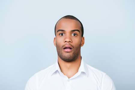 Close up portrait of astonished young freelancer mulatto guy, he stands in white smart shirt, on pure light background, shocked Foto de archivo