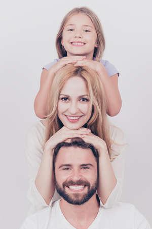 3의 가족 사진 초상화입니다. 부모와 작은 금발 딸은 웃고, 서로의 머리를 서로의 위에 두는 흰색 배경에 포즈를 취하고 있습니다.