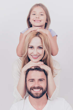 Family photo portrait of three. Parents and small blond daughter are posing on the white background, smiling, putting each others head on top of each other