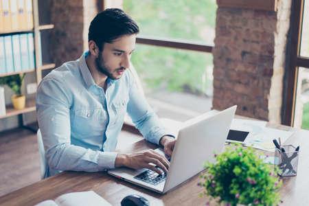 집중된 젊은 중동 사업가 사무실에서 자신의 노트북에 정보를 입력합니다. 그는 잘 생기고 성공하며 매우 세련된 사람입니다.