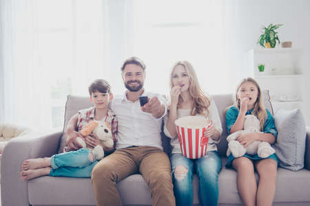 Happy family of four is watching interesting educational documentary, eating popcorn, at home on a couch