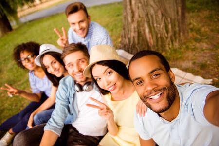 Zes internationale studenten met stralende glimlach poseren voor selfie-opname, die knappe Afrikaanse kerel neemt mee, buiten schoolgebouw. Verzamelde, vrolijke, slimme en succesvolle jeugd