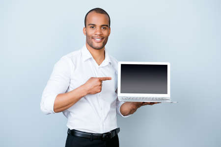 Young handsome mulatto banker on the pure light blue background is pointing on a laptop`s monitor with his finger, wearing white strict shirt Stock Photo