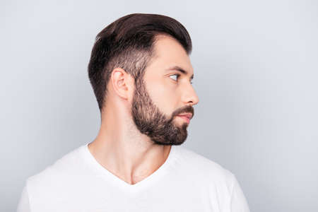 he: Advertising barbershop concept. Profile side portrait of handsome brunet bearded young man. He has a perfect stunning hair cut, in white t shirt isolated on light grey backgroung