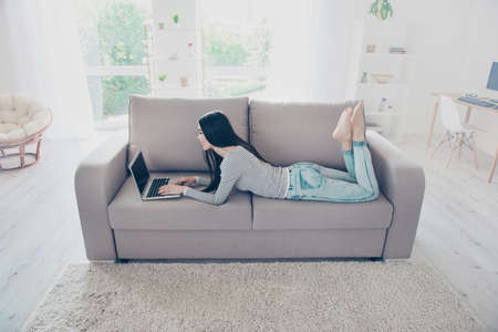Domestic life. Relaxed young asian lady is studying, lying on the cozy beige couch in living room at home, so comfortable atmosphere for study and work