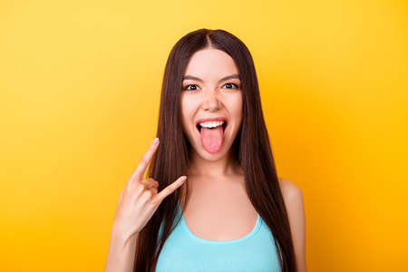Rock n roll babe! Attractive young asian mixed raced lady is posing on the camera, flirty and playful. In casual wear, on bright yellow background, showing rock sign with tongue out Stock Photo