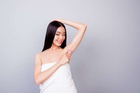 So smooth and pure. Young cute asian lady with pink shaver is cutting her armpit hair, smiling, standing in the towel, on pure background