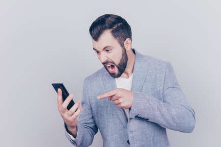 Going crazy and insane, psycho and agression. Close up portrait of shouting stressed young brunet bearded entrepreneur, pointing at his phone, on pure light background, wearing casual smart