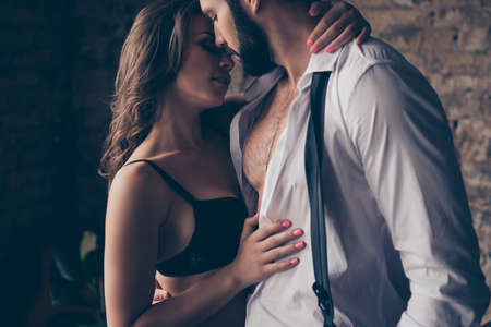 Pure seduction. Cropped close up photo of two naughty lovers, she is gorgeous in black lingerie, he is a business man in classy wear, they are so hot, horny and seductive 版權商用圖片 - 86370560
