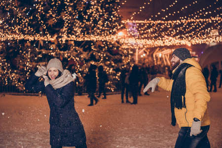Young handsome red bearded boyfriend is throwing a snow ball into his cute lover, wearing winter warm outfits, behind them are christmas illuminations Zdjęcie Seryjne - 87067477