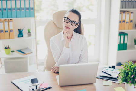 Portrait of serious young brunette businesswoman realtor in formal wear, sitting at her work place and concentrated, in glasses, in front of laptop