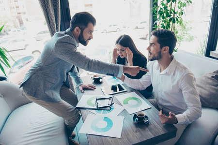 怒っている若いブリュネ髭の起業家は彼を非難し、彼のパートナーを指しています。