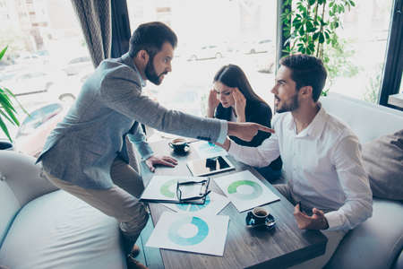 Angry young brunet bearded entrepreneur is pointing at his partner, blaming him.