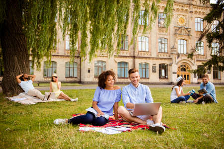Couples of multi ethnic students are preparing for test, sitting in the park, chatting, smile, enjoying, helping each other with studies. All dressed in comfortsble casual wear, behind is the college building Stock Photo