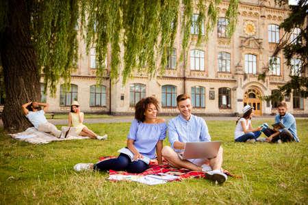 Parejas de estudiantes multiétnicos se preparan para la prueba, se sientan en el parque, charlan, sonríen, disfrutan, se ayudan entre sí con los estudios Todos vestidos con ropa casual cómoda, detrás está el edificio de la universidad.