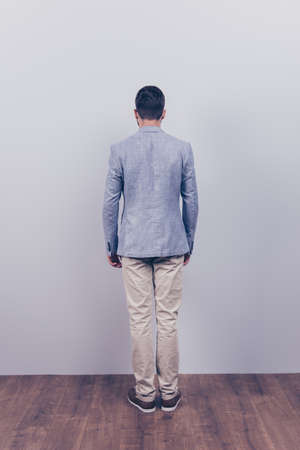 Snap model shot. Full length photo, rear view, guy in a formal wear, stands on a wooden floor, near the grey wall Stock Photo