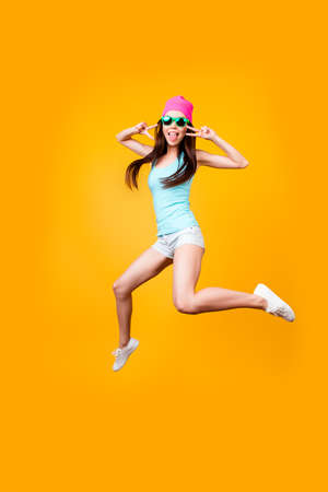 Funky, happiness, dream, fun, joy concept. Very excited happy cute asian teen is jumping up, showing v signs, on bright yellow background