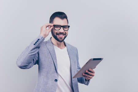 Cheerful handsome young black broker is looking at the camera, holding his tablet, standing in a casual smart on the pure background. So successful and intelligent, stylish and friendly