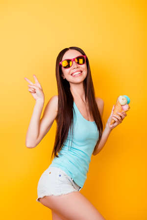 Funky young asian lady is posing for vacation photo shot, wearing tourist`s outfit, glasses, holds ice cream, has a tempting sexy pose Imagens