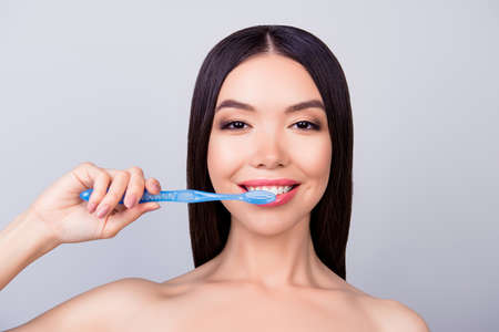 Dental health concept. Gorgeous asian girl is cleaning her teeth with blue tooth brush, on light grey background, she has a beaming smile Stock Photo